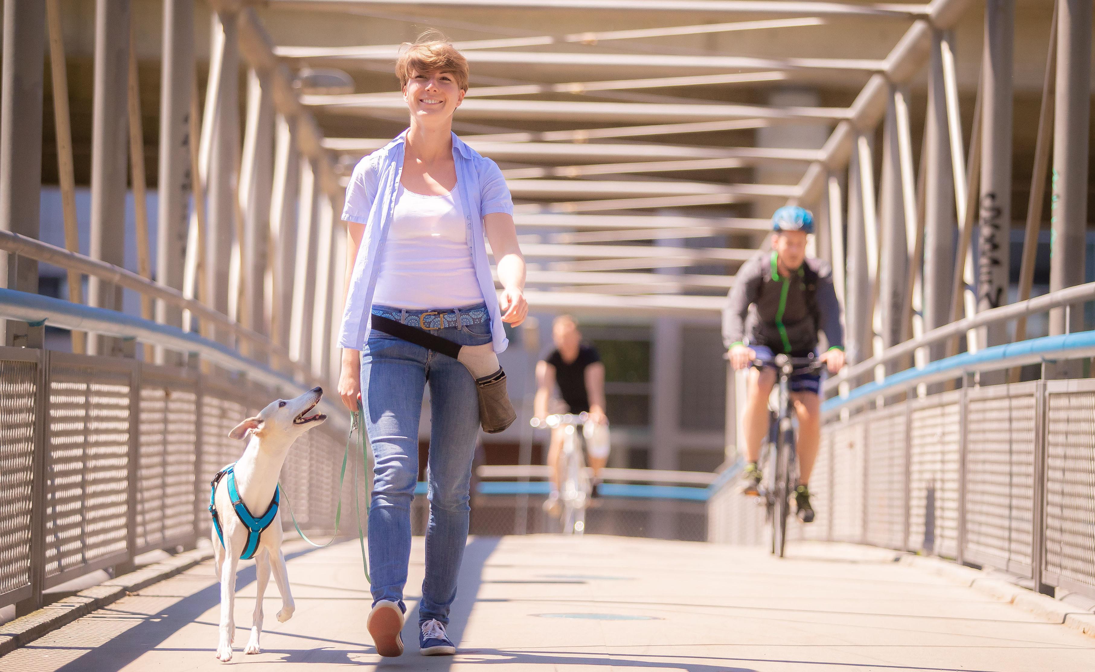 Frau mit Hund an der Leine geht entspannt über eine Donaukanal-Brücke, während aus dem Hintergrund Radfahrer das Duo passieren