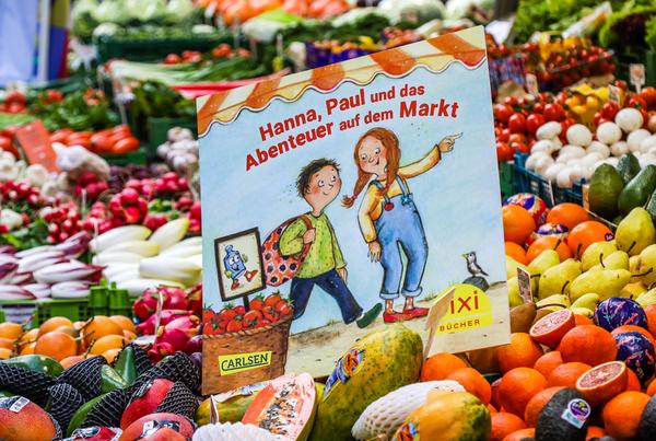 Das Pixi-Buch der TOW an einem Markstand zwischen Obst