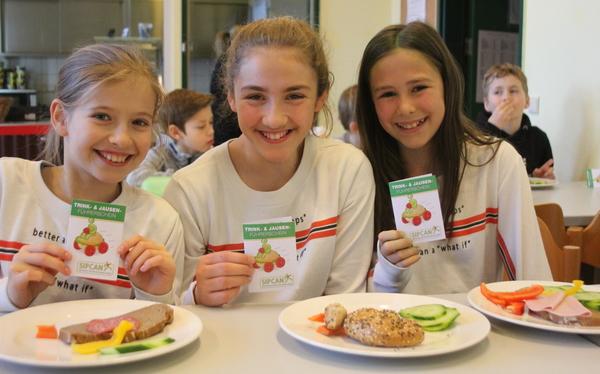 Drei Mädchen zeigen vor gesundem Jausenteller ihren Jausenführerschein