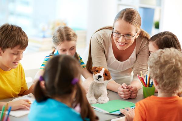 Frau mit Plüschhund steht lächelnd an einem Tisch mit SchülerInnen